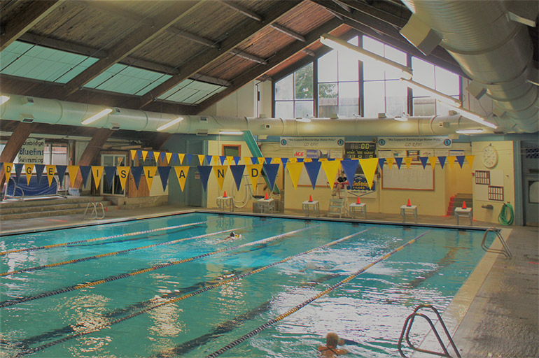 Inside of Ray Williamson Pool with flags above the racing lanes and a swimmer in one lane