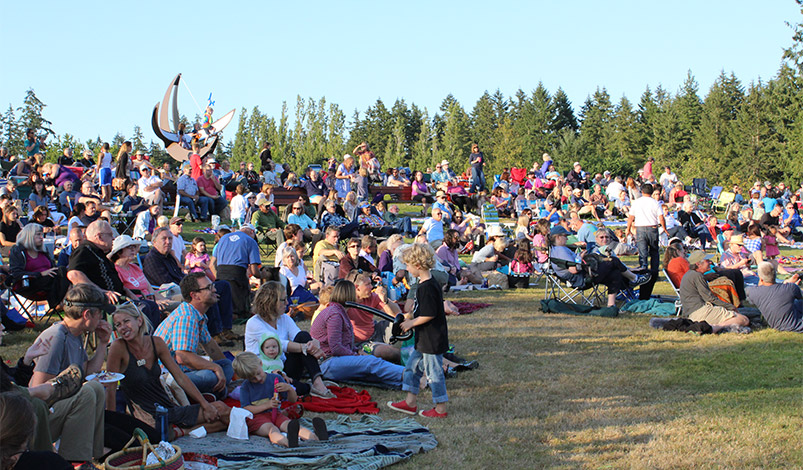 A crowd of people on blankets and chairs gather on a lawn on a sunny day at a concert in the park