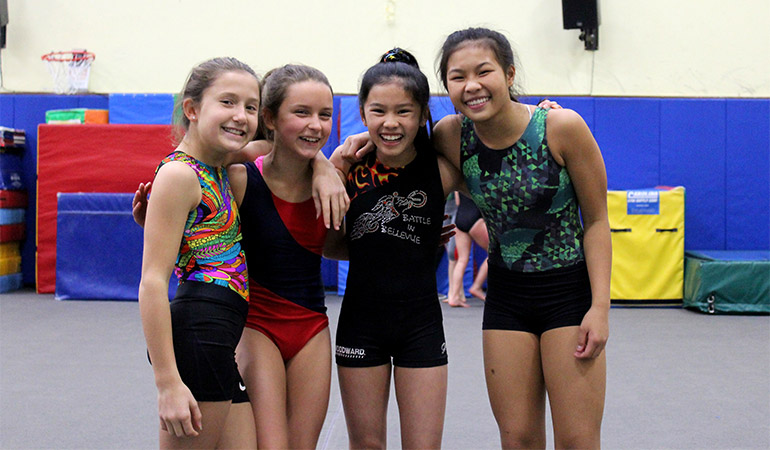 Young members of the gymnastics team smile together
