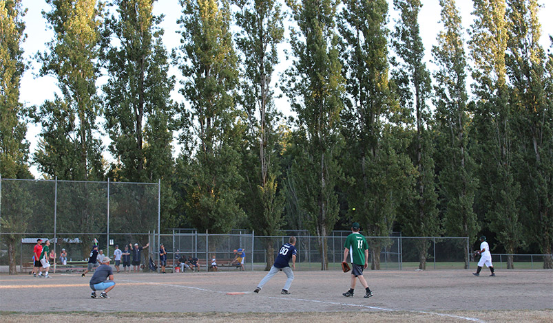 Adults practice in the softball diamond